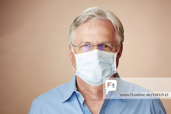 Grey-haired man with face mask looks into camera