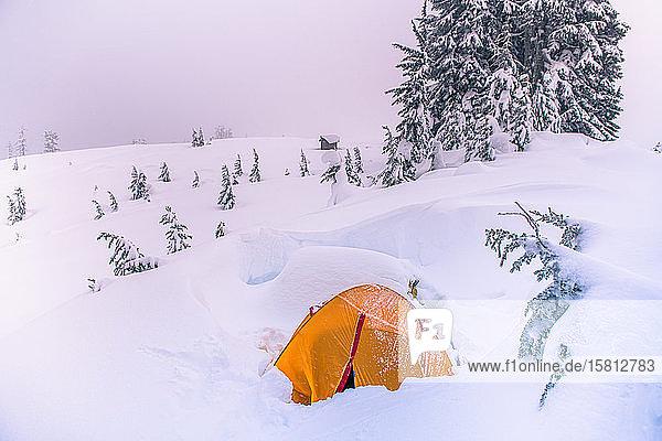 Hochwinkelansicht eines orangefarbenen Zeltes  das in einer winterlichen Landschaft aufgestellt ist.