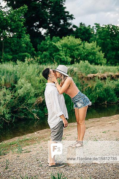 Junges Paar steht an einem Flussufer und küsst sich.