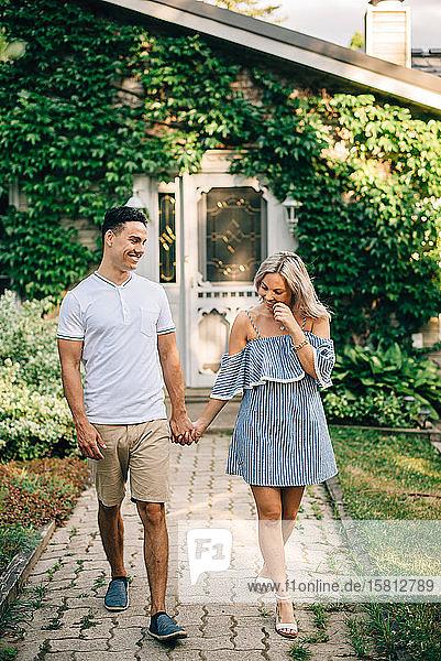 Junges Paar geht Hand in Hand vor der Hütte.