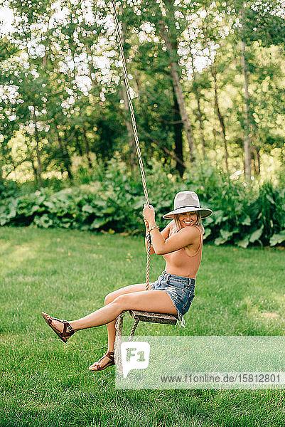Junge Frau mit Hut  die auf einer Schaukel in einem Park sitzt und lächelt.