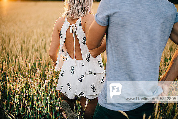 Rear view of young couple walking through a golden wheat field.