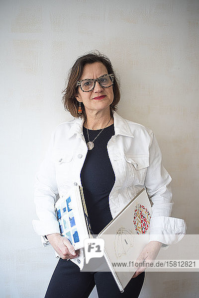 Portrait of brunette woman wearing glasses and white denim jacket  holding artist's sketch books.