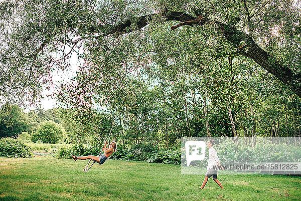 Junger Mann schubst junge Frau auf einer Schaukel in einem Park.