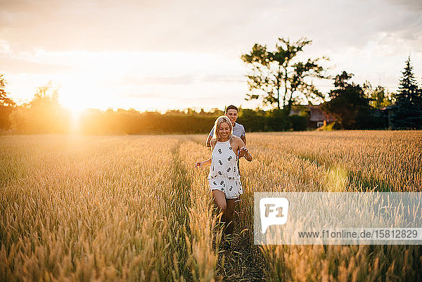 Smiling young couple walking through golden wheat field at sunset.
