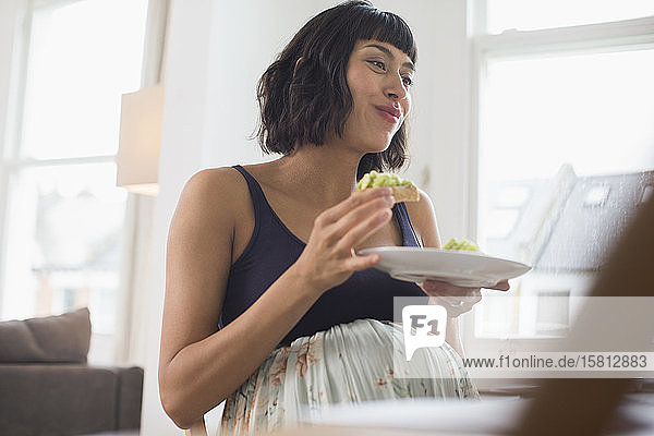 Happy pregnant woman eating