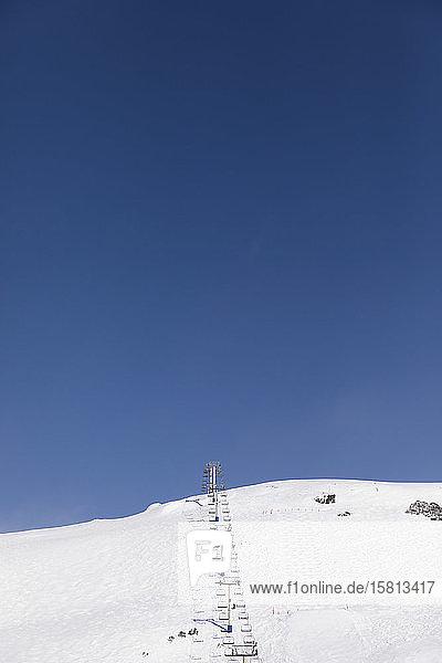 Skilift auf verschneitem Berghang unter sonnigem blauem Himmel  Falls Creek  Victoria  Australien