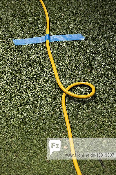 Gelbes Verlängerungskabel mit Klebeband am Gras