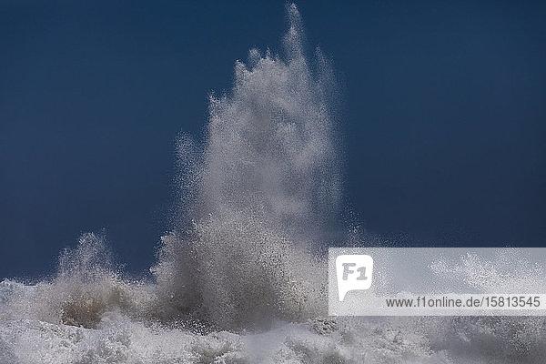 Mächtige Meereswelle  die sich am blauen Himmel bricht