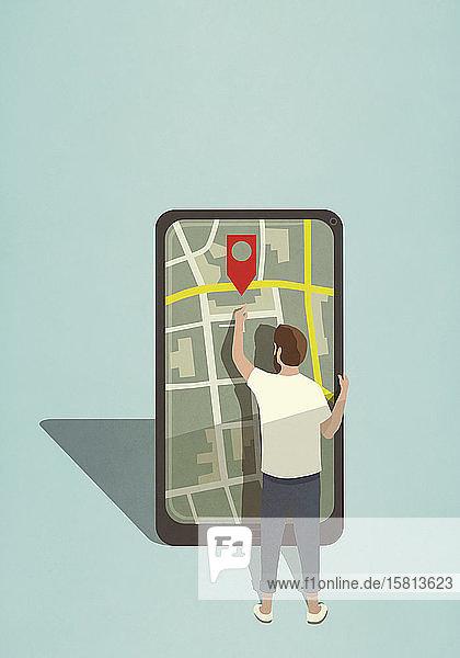 Mann greift nach dem Symbol einer Kartennadel auf einem großen Smartphone