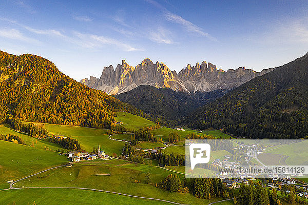 Sunset on the little village of Santa Magdalena and Odle peaks in autumn  aerial view  Funes  Dolomites  South Tyrol  Italy  Europe