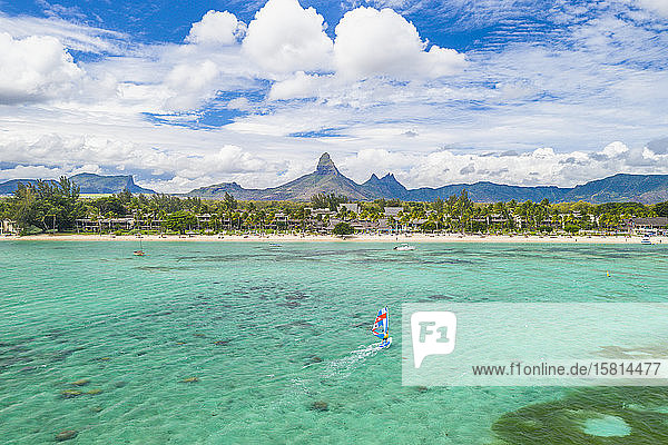 Aerial view by drone of windsurfer in the lagoon facing Flic en Flac beach and Piton de la Petite Riviere Noire mountain  Black River  Mauritius  Indian Ocean  Africa