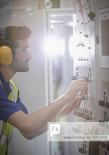Male worker wearing ear protectors  operating machinery at control panel in factory Male worker wearing ear protectors, operating machinery at control panel in factory