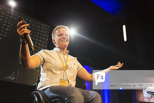 Smiling  confident female speaker with microphone in wheelchair on stage