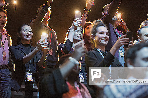 Smiling audience with camera phone flashlights in dark auditorium