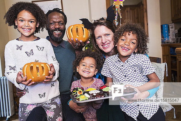 Portrait happy family with carved pumpkins and Halloween cupcakes Portrait happy family with carved pumpkins and Halloween cupcakes