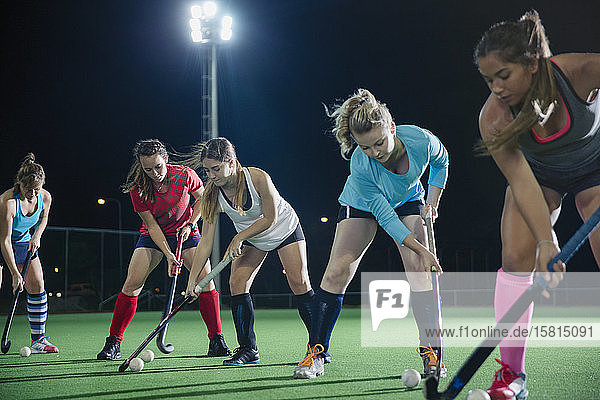 Focused young female field hockey players practicing sports drill on field at night