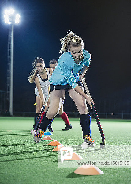 Determined young female field hockey player practicing sports drill on field at night
