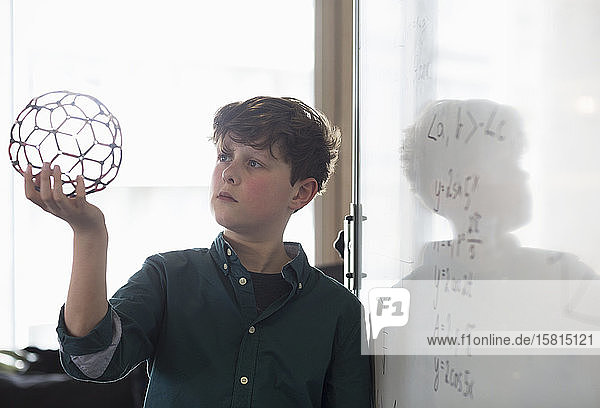 Serious boy student holding molecular structure in classroom Serious boy student holding molecular structure in classroom
