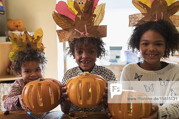 Portrait happy brother and sisters with turkey hats and pumpkins