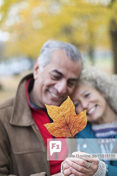 Affectionate senior couple holding orange autumn leaf