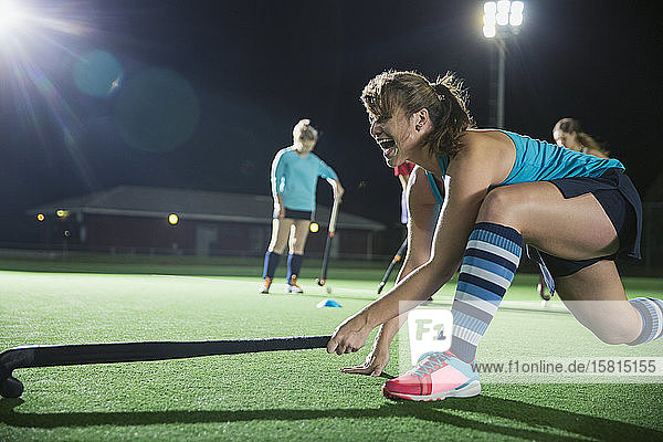 Determined female field hockey player reaching with hockey stick
