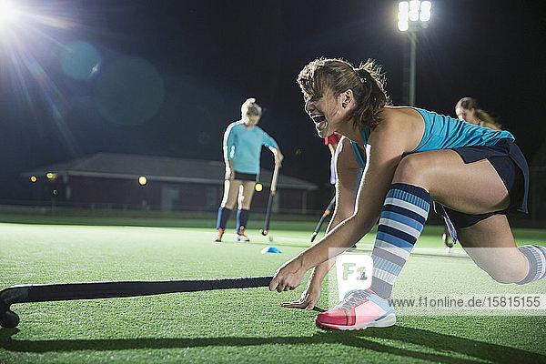 Determined female field hockey player reaching with hockey stick Determined female field hockey player reaching with hockey stick