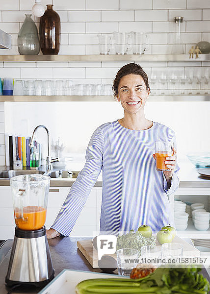 Portrait smiling  confident brunette woman drinking healthy carrot juice at blender in kitchen