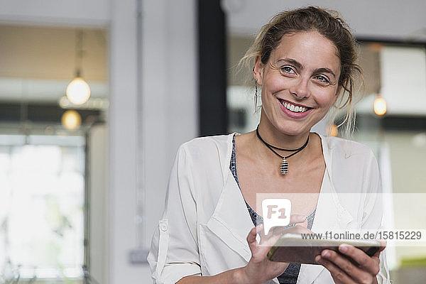 Portrait smiling businesswoman using digital tablet