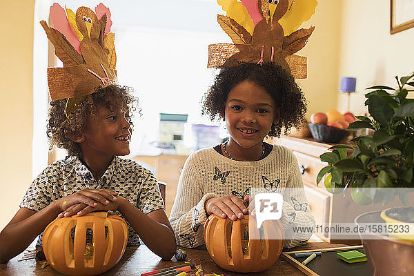 Portrait happy brother and sister with turkey hats carving pumpkins Portrait happy brother and sister with turkey hats carving pumpkins