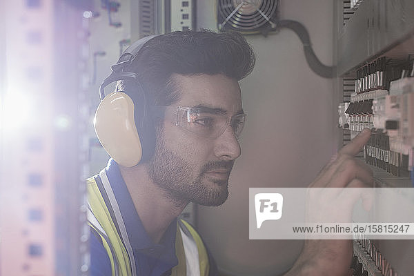 Serious male worker wearing ear protectors operating machinery at control panel in factory