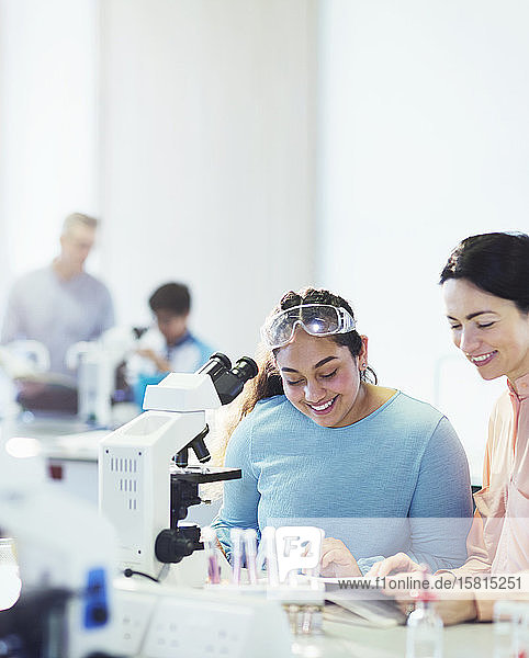 Smiling female science teacher and girl student reading textbook at microscope in laboratory classroom