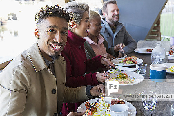 Portrait smiling young man eating breakfast with friends at restaurant outdoor patio