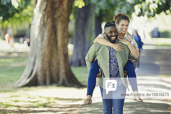 Playful young couple piggybacking in park