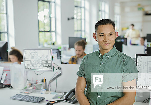 Portrait confident male architect in open plan office