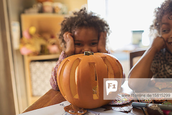 Portrait cute girl carving Halloween pumpkin at table