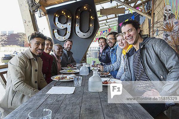 Portrait smiling friends eating at restaurant outdoor patio Portrait smiling friends eating at restaurant outdoor patio