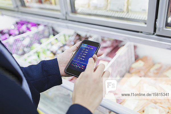 Woman using shopping list app  shopping in supermarket Woman using shopping list app, shopping in supermarket