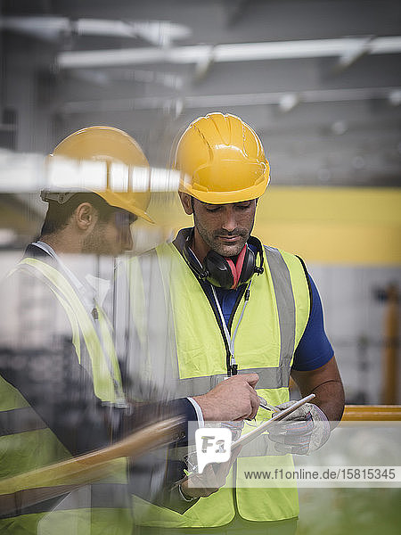 Male supervisor and worker with clipboard talking in factory Male supervisor and worker with clipboard talking in factory