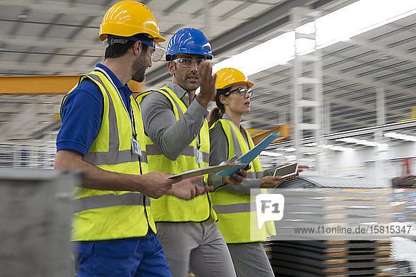 Supervisors with clipboard and digital tablet walking in warehouse Supervisors with clipboard and digital tablet walking in warehouse
