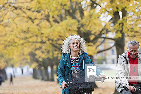 Smiling  carefree senior woman bike riding among trees in autumn park