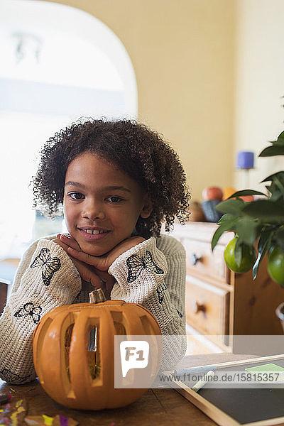 Portrait confident girl carving pumpkin at table Portrait confident girl carving pumpkin at table