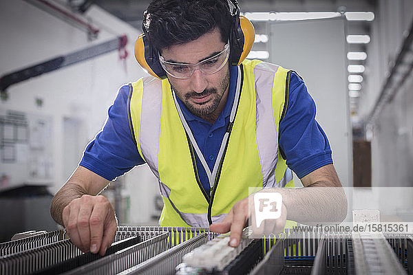 Male engineer assembling equipment in factory Male engineer assembling equipment in factory