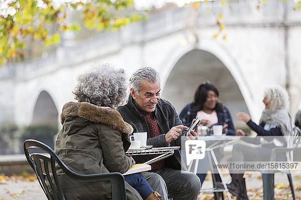 Active senior couple using smart phone  drinking coffee at autumn park cafe