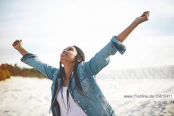Exuberant young woman with arms outstretched on beach