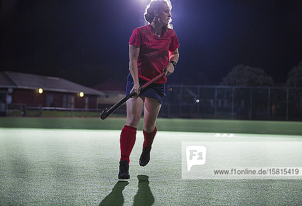 Young female field hockey player running with hockey stick on field at night Young female field hockey player running with hockey stick on field at night