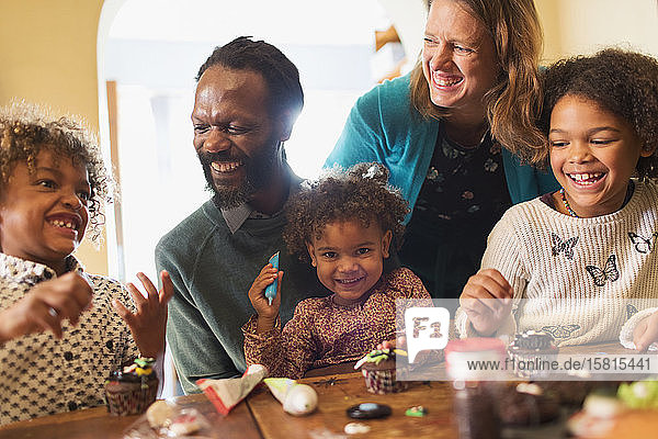 Happy multiethnic family decorating cupcakes at table
