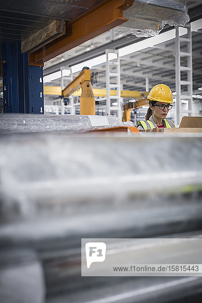Focused female worker using laptop in steel factory