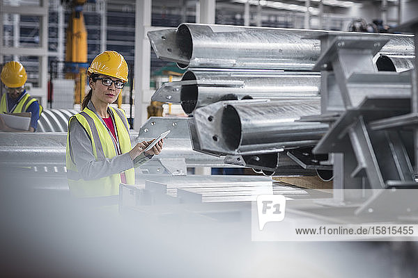 Portrait confident female worker with digital tablet in steel factory