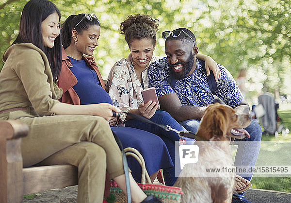 Smiling friends with dog using smart phone in park